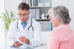 Arts die voorschriften verklaren aan hogere vrouw Stock Afbeeldingen