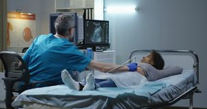 Arts die vrouw met ultrasone klank onderzoeken stock video