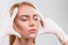 Arts die vrouwelijke huid controleren vóór plastische chirurgie royalty-vrije stock afbeelding