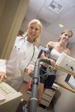 Arts die Vrouwelijke Patiënt op Tredmolen controleert Stock Foto's