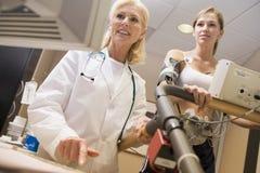 Arts die Vrouwelijke Patiënt op Tredmolen controleert Royalty-vrije Stock Afbeelding