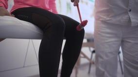 Arts die zenuwreflexen met de vrouw van de hamertherapie A controleren bij de spreekkamer De artsenslagen met een hamer  stock footage