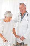 Arts die zijn patiënt helpt te lopen royalty-vrije stock afbeelding