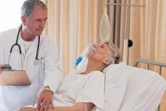 Arts die zijn patiënt onderzoekt Stock Foto's