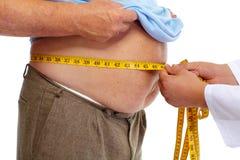 Arts die zwaarlijvige mensenmaag meten Stock Foto