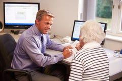 Arts Discussing Test Results met Hogere Vrouwelijke Patiënt stock afbeeldingen