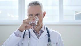 Arts Drinking Water in Kliniek royalty-vrije stock afbeelding