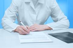 Arts in een witte laag bij de lijst en de tekens een x-ray examen Close-up royalty-vrije stock afbeeldingen