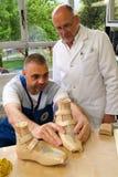 Arts en arbeider die orthopedische binnenzolen voor een patiënt voorbereiden royalty-vrije stock foto