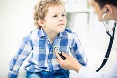 Arts en geduldig kind Arts die weinig jongen onderzoeken Regelmatig medisch bezoek in kliniek Geneeskunde en gezondheidszorg stock foto's