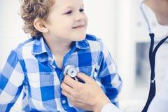 Arts en geduldig kind Arts die weinig jongen onderzoeken Regelmatig medisch bezoek in kliniek Geneeskunde en gezondheidszorg royalty-vrije stock fotografie