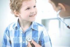 Arts en geduldig kind Arts die weinig jongen onderzoeken Regelmatig medisch bezoek in kliniek Geneeskunde en gezondheidszorg royalty-vrije stock afbeeldingen