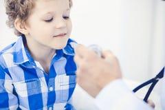 Arts en geduldig kind Arts die weinig jongen onderzoeken Regelmatig medisch bezoek in kliniek Geneeskunde en gezondheidszorg stock afbeelding