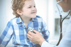 Arts en geduldig kind Arts die weinig jongen onderzoeken Regelmatig medisch bezoek in kliniek Geneeskunde en gezondheidszorg royalty-vrije stock foto