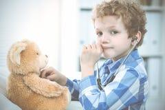 Arts en geduldig kind Arts die weinig jongen onderzoeken Regelmatig medisch bezoek in kliniek Geneeskunde en gezondheidszorg stock afbeeldingen