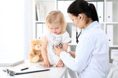 Arts en geduldige baby in het ziekenhuis Het meisje wordt onderzocht door pediater met stethoscoop Vertragingen en wapens royalty-vrije stock afbeeldingen