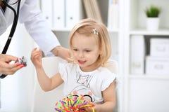 Arts en geduldige baby in het ziekenhuis Het meisje wordt onderzocht door pediater met stethoscoop Vertragingen en wapens stock afbeelding