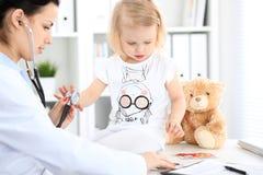 Arts en geduldige baby in het ziekenhuis Het meisje wordt onderzocht door pediater met stethoscoop Vertragingen en wapens royalty-vrije stock foto's