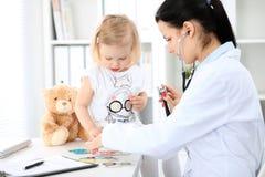 Arts en geduldige baby in het ziekenhuis Het meisje wordt onderzocht door pediater met stethoscoop Vertragingen en wapens royalty-vrije stock foto