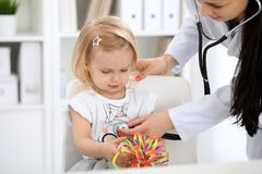Arts en geduldige baby in het ziekenhuis Het meisje wordt onderzocht door pediater met stethoscoop Vertragingen en wapens stock foto's