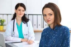 Arts en patiënt die een bespreking hebben terwijl het zitten bij het bureau Nadruk op jonge mooie vrouw die camera bekijken genee stock foto