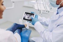 Arts en patiënt die het tabletscherm bekijken royalty-vrije stock foto