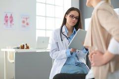 Arts en patiënt die iets bespreken terwijl het zitten bij de lijst Geneeskunde en gezondheidszorgconcept Royalty-vrije Stock Fotografie