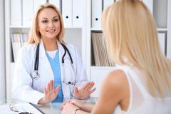Arts en patiënt die iets bespreken terwijl het zitten bij de lijst bij het ziekenhuis Geneeskunde en gezondheidszorgconcept stock foto