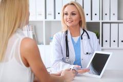 Arts en patiënt die iets bespreken terwijl het zitten bij de lijst bij het ziekenhuis Arts die tabletpc met behulp van voor stock fotografie