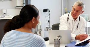Arts en patiënt die over medisch rapport bespreken stock footage