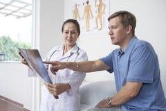 Arts en patiënt die röntgenstraal bespreken stock afbeeldingen