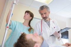 Arts en verpleegster die aan geduldige dragende halssteun neigen stock afbeelding