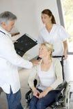 Arts en verpleegster die auto van patiënt in rolstoel nemen Royalty-vrije Stock Fotografie