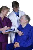 Arts en verpleegster die bejaarde patiënt onderzoeken Royalty-vrije Stock Foto