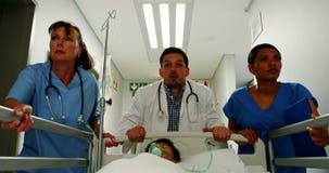 Arts en verpleegster die een patiënt in noodsituatieafdeling meeslepen stock video