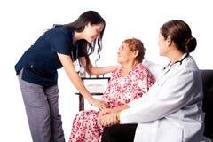 Arts en Verpleegster die Hogere Patiënt raadplegen Stock Foto's