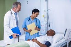 Arts en verpleegster die met patiënt tijdens bezoek in afdeling interactie aangaan stock foto's