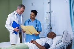 Arts en verpleegster die rapport bespreken tijdens bezoek in afdeling stock foto's