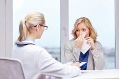 Arts en zieke vrouwenpatiënt met griep bij kliniek stock foto's
