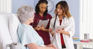 Arts en zwarte verpleegster die met bejaarde patiënt in het ziekenhuisbed spreken