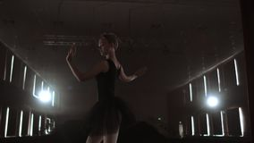 Arts and entertainment in theatre with female classic dancer in tutu, standing behind the scenes and looking at stalls. Arts and entertainment in theatre with stock video footage
