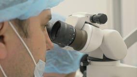 Arts gebruikte microscoop De tandarts behandelt patiënt in modern tandbureau Het Orthodontistwerk met medewerker verrichting stock footage