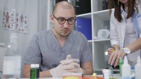 Arts in glazen en vrouw arts in het laboratorium Farmacologie en geneeskundeconcept stock footage