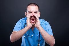 Arts het dragen schrobt met stethoscoop luid gillen uit stock afbeeldingen