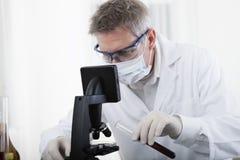 Arts het kijken op microscoop en analyseert bloed Stock Afbeeldingen