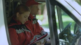 Arts het schrijven rapport in ziekenwagen, die aan camera, de hervorming van de noodsituatiegeneeskunde glimlachen stock footage