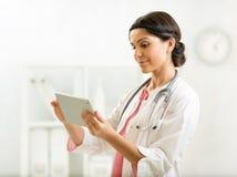 Arts in het ziekenhuisbureau die een digitale tablet gebruiken Stock Foto's