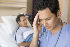 Arts kijkt die die in de Zaal van Patiënten wordt gefrustreerd Stock Afbeeldingen