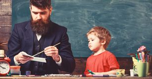 Arts lesson concept. Child and teacher on busy face painting, drawing. Teacher with beard, father drawing while little stock photo