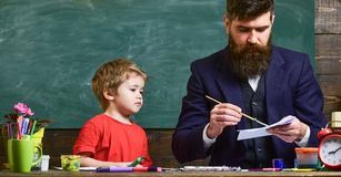 Arts lesson concept. Child and teacher on busy face painting, drawing. Teacher with beard, father drawing while little. Son hang out near, in classroom stock photos